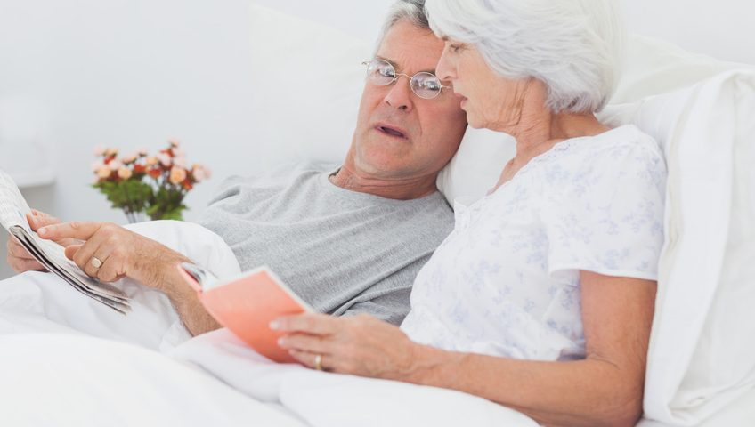 Mature couple looking at a newspaper in bed
